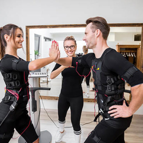 Happy man and woman doing exercises with ems devices